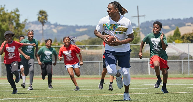 Boys and Girls Club kids chasing Davante Adams while he runs with football.