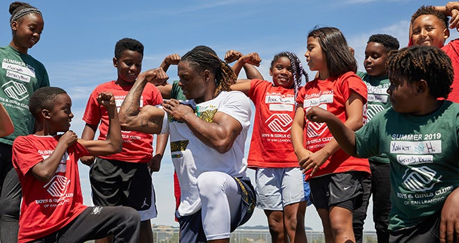 Davante Adams and Boys and Girls Club Kids flexing their biceps.